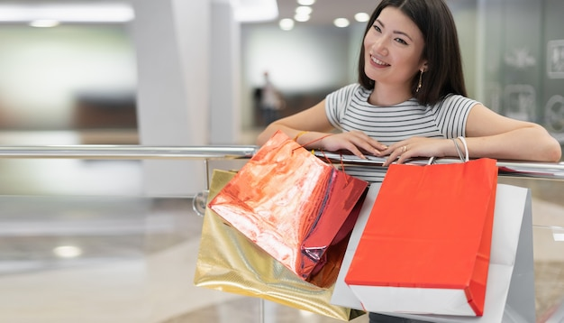 A korean woman is shopping at a mall. stands with paper bags in hand.