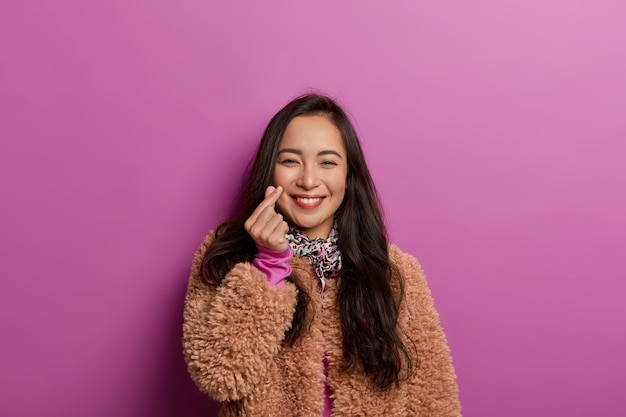 Korean woman shows mini heart sign, smiles tenderly, expresses affection and love during photoshoot