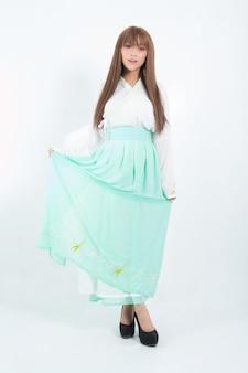スタジオで白に伝統的な韓国のドレスを着ている韓国人女性。