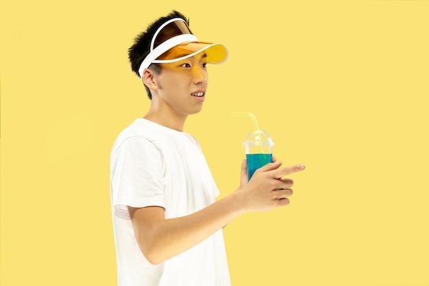 Поясной портрет корейского молодого человека на желтом студийном фоне. модель-мужчина в белой рубашке и желтой кепке. питьевой коктейль. понятие человеческих эмоций, выражения, лета, отпуска, выходных.