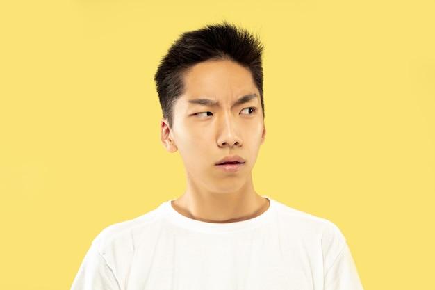 노란색 스튜디오 배경에 한국 젊은이의 절반 길이 초상화. 흰 셔츠에 남성 모델. 의심스럽고, 사려 깊고, 심각해 보입니다. 인간의 감정, 표정의 개념.