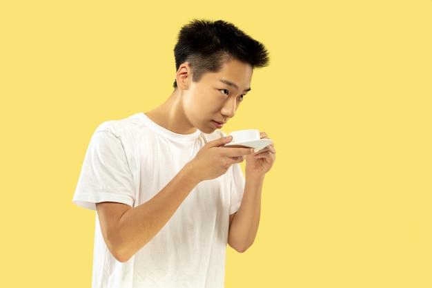 노란색 스튜디오 배경에 한국 젊은이의 절반 길이 초상화. 흰 셔츠에 남성 모델. 커피를 마시고 행복 함을 느낍니다. 인간의 감정, 표정의 개념. 전면보기. 트렌디 한 색상.