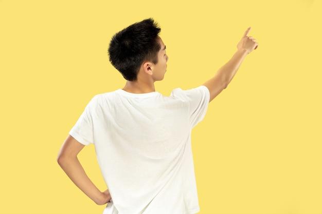 黄色のスタジオの背景に韓国の若い男の半身像。白いシャツの男性モデル。広告の場所を指しています。人間の感情、顔の表情の概念。トレンディな色。