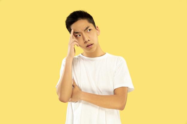 노란색 스튜디오 배경에 한국 젊은이의 절반 길이 초상화. 흰 셔츠에 남성 모델. 진지한 생각 또는 사려 깊음. 인간의 감정, 표정의 개념. 전면보기. 트렌디 한 색상.