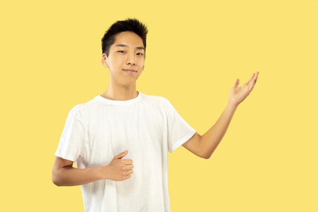 노란색 스튜디오 배경에 한국 젊은이의 절반 길이 초상화. 흰 셔츠에 남성 모델. 뭔가 보여주는. 인간의 감정, 표정의 개념. 전면보기. 트렌디 한 색상.