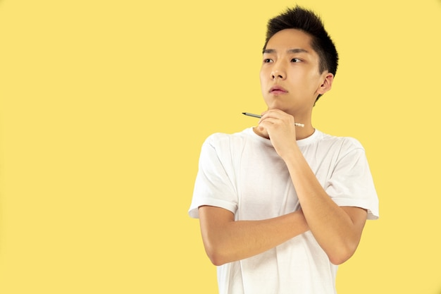 노란색 스튜디오 배경에 한국 젊은이의 절반 길이 초상화. 흰 셔츠에 남성 모델. 팬 실로 사려 깊게 서 있습니다. 인간의 감정, 표정의 개념. 전면보기.