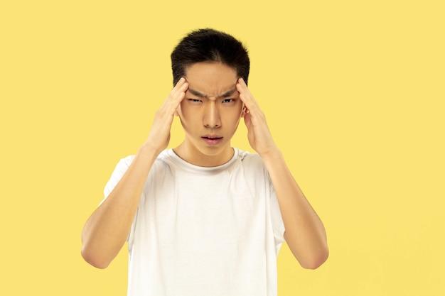 노란색 스튜디오 배경에 한국 젊은이의 절반 길이 초상화. 흰 셔츠에 남성 모델. 진지하게 생각합니다. 인간의 감정, 표정의 개념. 전면보기. 트렌디 한 색상.