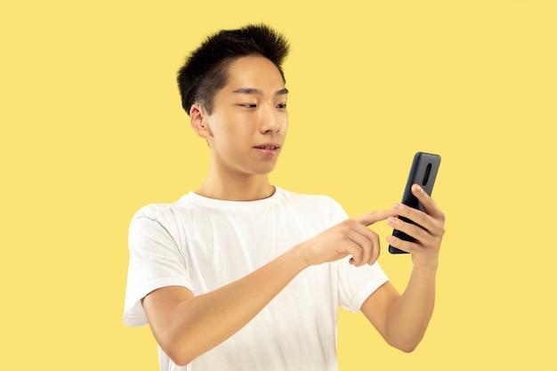 黄色のスタジオの背景に韓国の若い男の半身像。白いシャツの男性モデル。スマートフォンを使う。人間の感情、顔の表情の概念。正面図。トレンディな色。