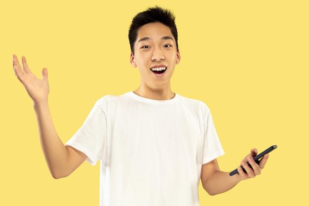 黄色のスタジオの背景に韓国の若い男の半身像。白いシャツの男性モデル。賭け、ニュースの閲覧、会話にスマートフォンを使用する。人間の感情、顔の表情の概念。