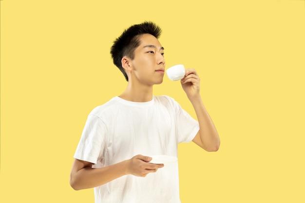 黄色の壁に韓国の若い男の半身像