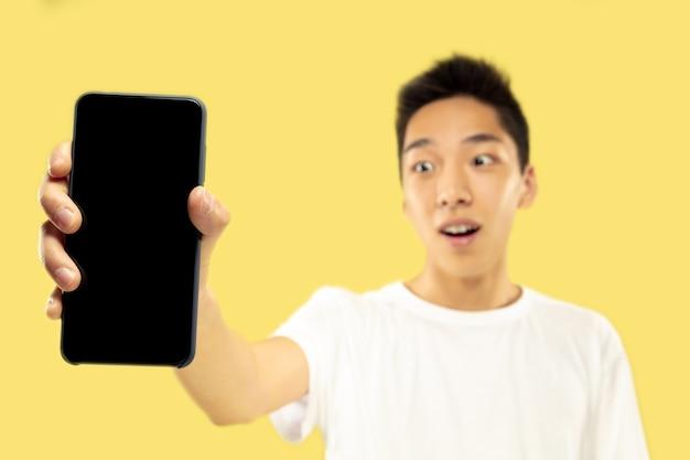 노란색 벽에 한국 젊은이의 절반 길이 초상화