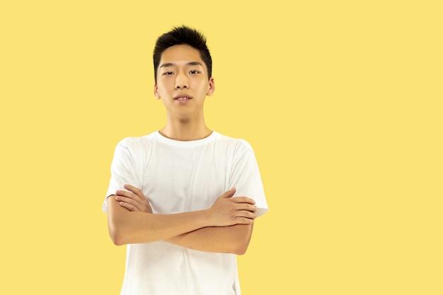 Ritratto a mezzo busto del giovane coreano su sfondo giallo studio. modello maschile in camicia bianca. in piedi e guardando. concetto di emozioni umane, espressione facciale. vista frontale. colori alla moda.