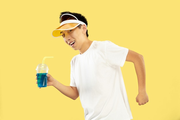 Ritratto a mezzo busto del giovane coreano su sfondo giallo studio. modello maschile in camicia bianca e berretto giallo. bere cocktail. concetto di emozioni umane, espressione, estate, vacanza, fine settimana.