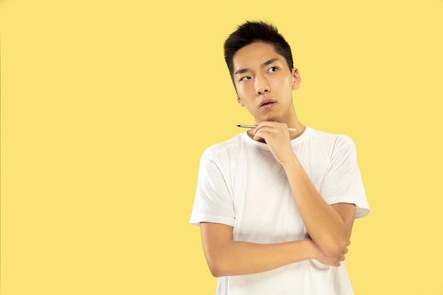 Ritratto a mezzo busto del giovane coreano su colore giallo