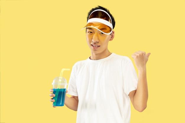 Портрет корейского молодого человека. модель-мужчина в белой рубашке и желтой кепке. питьевой коктейль. понятие человеческих эмоций, выражения, лета, отпуска, выходных.