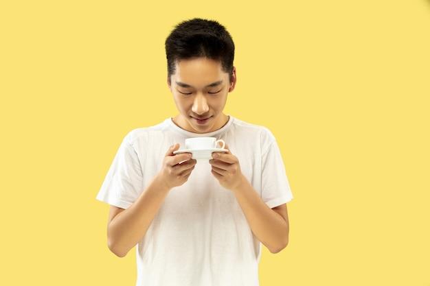 韓国の若者の肖像画。白いシャツの男性モデル。コーヒーを飲み、幸せを感じます。人間の感情、顔の表情の概念。正面図。トレンディな色。
