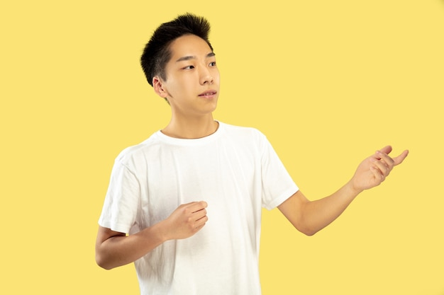 한국 청년의 초상화. 흰 셔츠에 남성 모델. 뭔가 보여주는. 인간의 감정, 표정의 개념. 전면보기. 트렌디 한 색상.