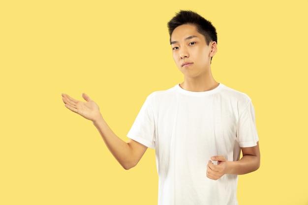 Портрет корейского молодого человека. мужская модель в белой рубашке. показывает что-то. понятие о человеческих эмоциях, выражении лица. передний план. модные цвета.