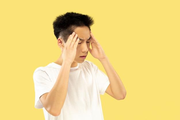 한국 청년의 초상화. 흰 셔츠에 남성 모델. 진지하게 생각합니다. 인간의 감정, 표정의 개념. 전면보기. 트렌디 한 색상.