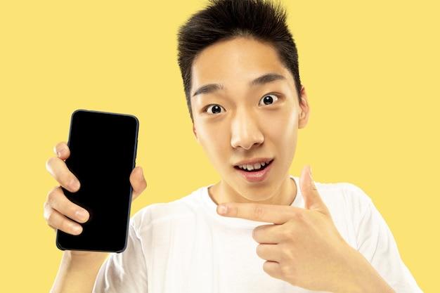 Ritratto del giovane coreano. modello maschile in camicia bianca. utilizzo dello smartphone per scommettere, leggere notizie o parlare. concetto di emozioni umane, espressione facciale.