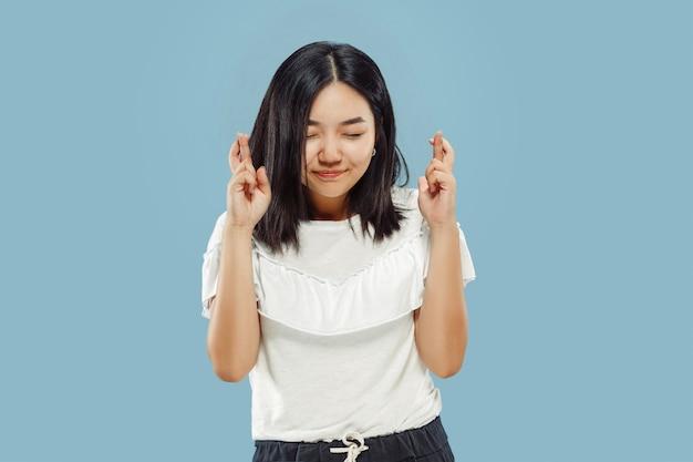 韓国の若い女性の半身像。白いシャツの女性モデル。勝者のように祝って、幸せそうに見えます。人間の感情、顔の表情の概念。正面図。