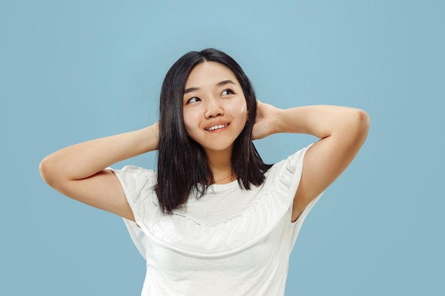 韓国の若い女性の半身像。白いシャツの女性モデル。休憩と笑顔。人間の感情、顔の表情の概念。正面図。