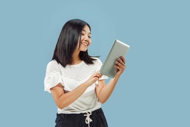 푸른 공간에 한국 젊은 여성의 절반 길이 초상화. 흰 셔츠에 여성 모델입니다. 태블릿을 사용하고 웃고 있습니다.