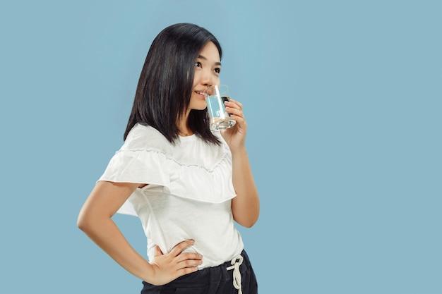 青いスタジオで韓国の若い女性の半身像