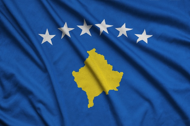 Kosovo flag is depicted on a sports cloth fabric with many folds.