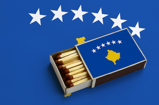 Kosovo flag  is shown in an open matchbox, which is filled with matches and lies on a large flag