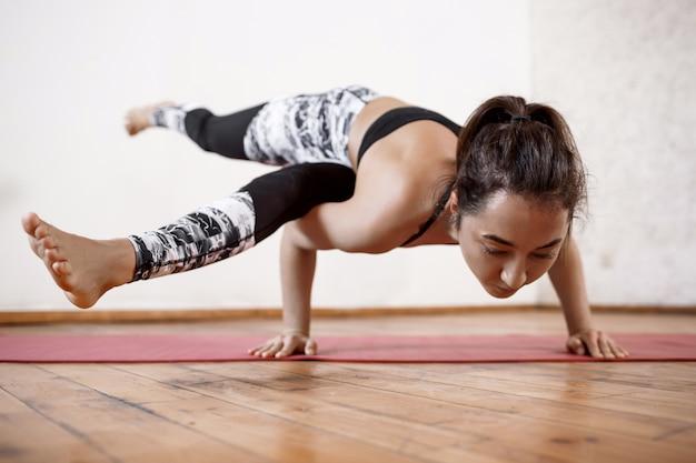 屋内ヨガアームバランスアーサナエカパダkoundiyanasanaを練習する若い美しいスポーツ女性