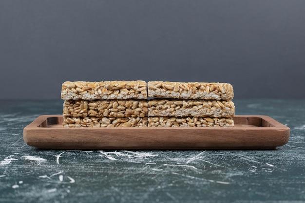Конфеты козинаки с семенами и орехами на деревянной тарелке.