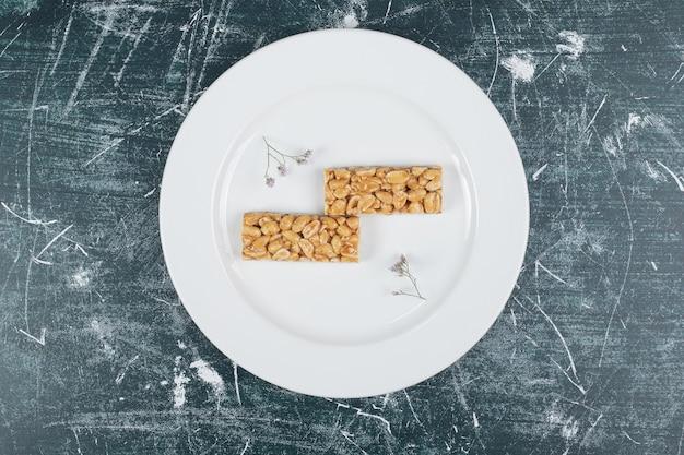 Конфеты козинаки с орехами на белой тарелке. фото высокого качества