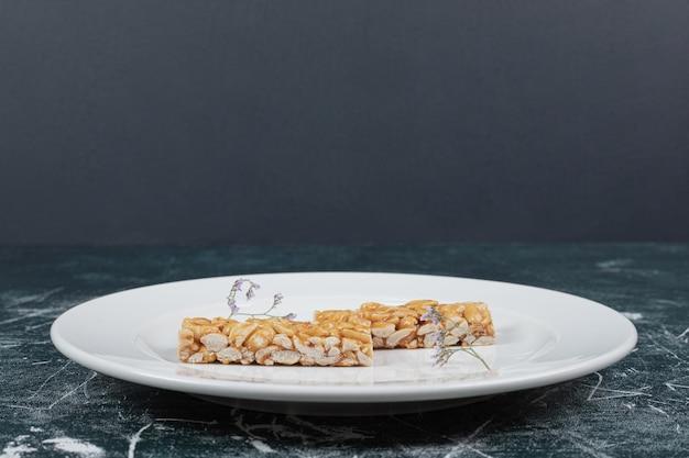 Конфеты козинаки с орехами на белой тарелке.