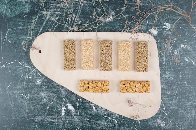 Конфеты козинаки с семенами и орехами на деревянной доске. фото высокого качества