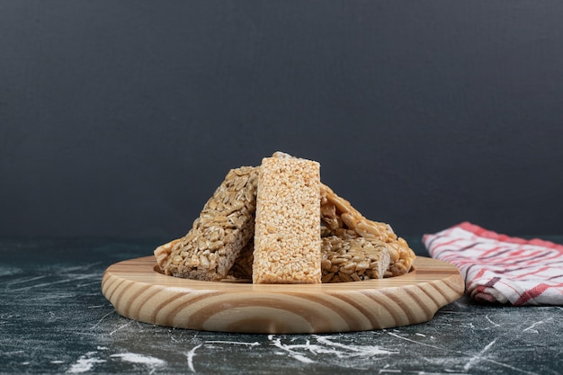 Конфеты козинаки с семенами и орехами на деревянной тарелке. фото высокого качества