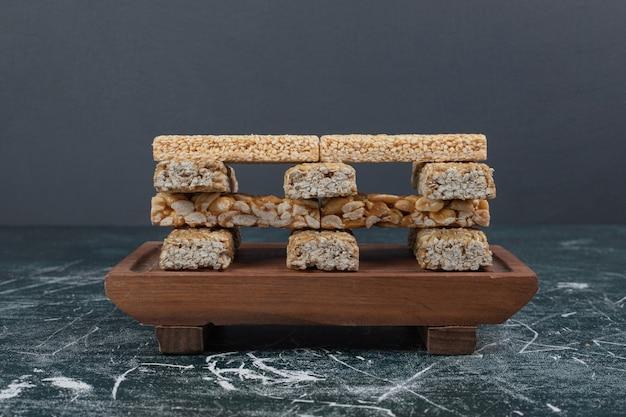 Конфеты козинаки с семенами и арахисом на деревянной доске.