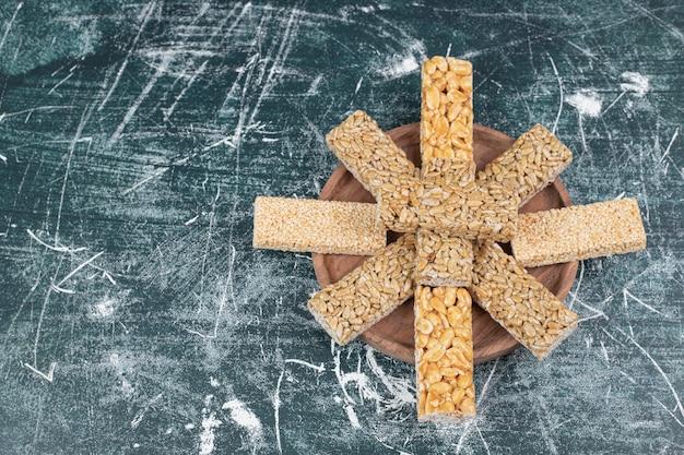Конфеты козинаки с семенами и арахисом на деревянной тарелке. фото высокого качества