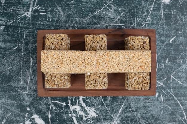 Dolci kozinaki con semi e noci sul piatto di legno. foto di alta qualità