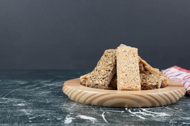 Dolci kozinaki con semi e noci sul piatto di legno.
