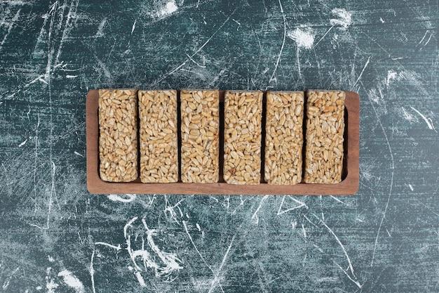 Конфеты козинаки с семенами на деревянной тарелке. фото высокого качества