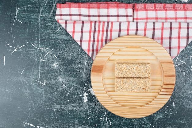 Dolci kozinaki con semi sul piatto di legno.