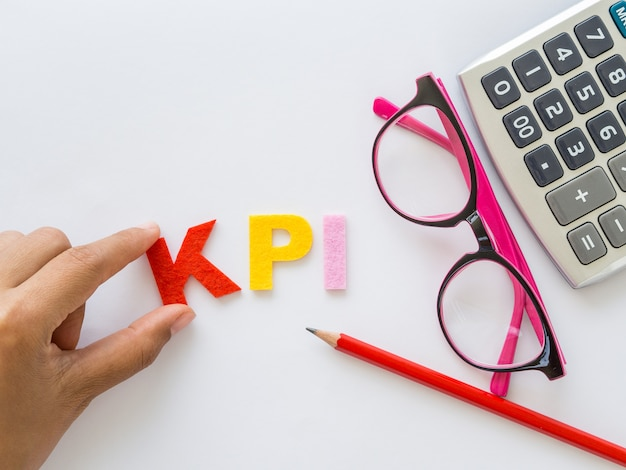 Kpi alphabet with red pencil and pink glasses put on white table background