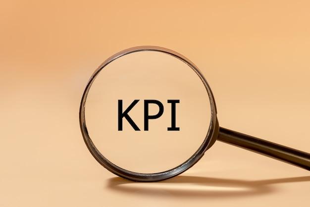 虫眼鏡に黒い文字で書かれたkpiの碑文。主要業績評価指標の概念。