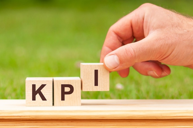 Kpi is a word written on wooden blocks. a man's hand holds a wooden cube with the letter i from the word kpi