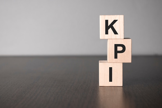 Kpi wooden blocks with letters, key performance indicator kpi concept, top view on grey background