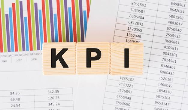 나무 블록에 쓰여진 kpi 단어. 테이블에 자주 묻는 질문 텍스트, 개념.