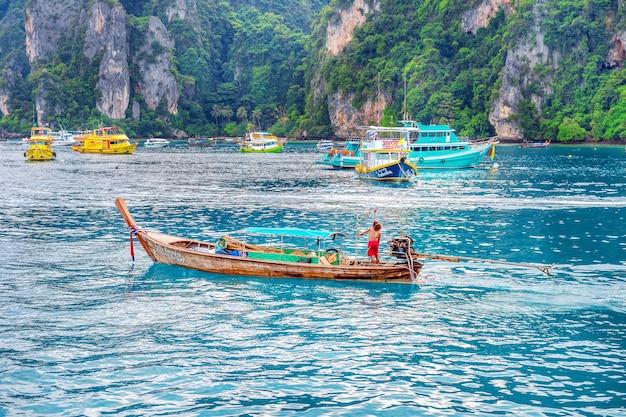 Краби - 1-ое декабря: длинная лодка и турист в заливе майя на острове пхи-пхи. фотография сделана 1 декабря 2016 года в краби, таиланд.
