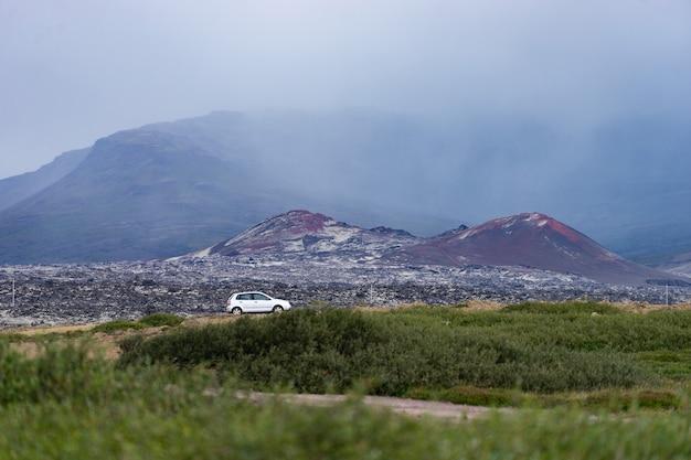 アイスランド、クラプラ火山の風景カラフルで鮮やかな赤いミネラルの丘とミーバトン湖近くの道路高速道路の高角度ビュー