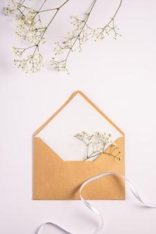 Конверт из крафт-бумаги с белой пустой карточкой, цветами гипсофилы и тканевой лентой, белый фон, макет пустое письмо